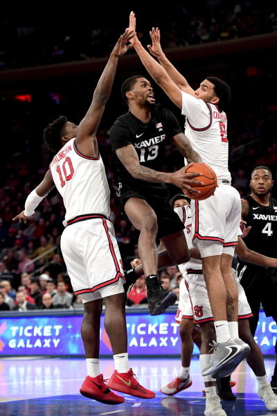 Xavier's Naji Marshall (13) attempts a lay up against St. John's Marcellus Earlington (10) and Julian Champagnie (2) during an NCAA college basketball game in New York on Monday, Feb 17, 2020. (Steven Ryan/Newsday via AP)