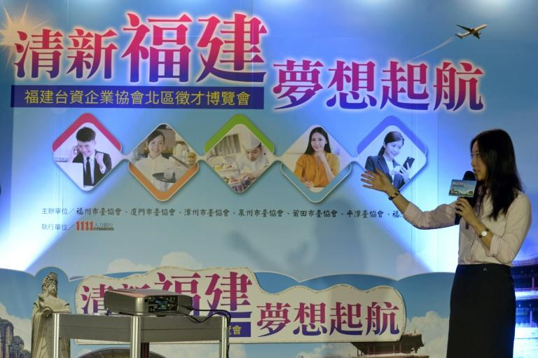 """A woman introduces mainland openings at a jobs fair in Taipei. China is wooing young Taiwanese talent in what analysts say is a """"soft power"""" push to sway political sentiment"""