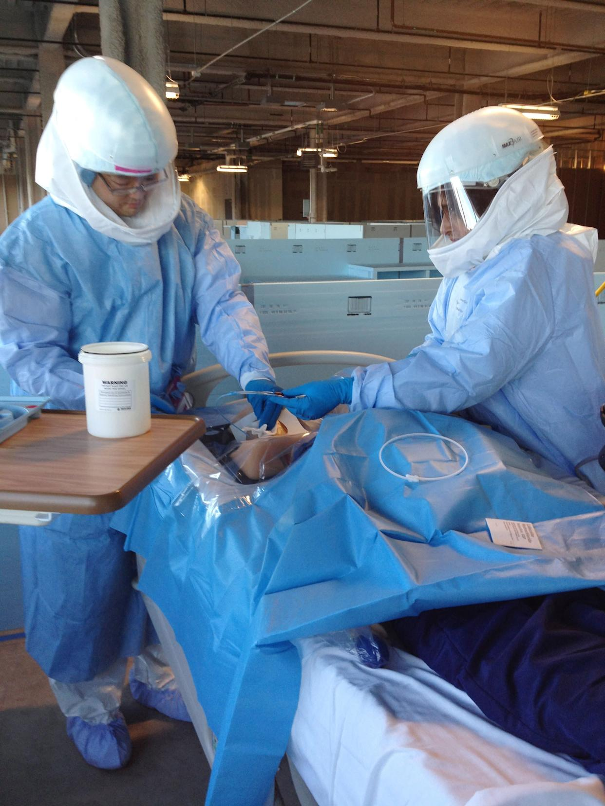 In this Monday, Oct. 6, 2014, photo Dr. Mark Abe, left, and Dr. Neethi Pinto learn how to perform a medical procedure on a patient mannequin while wearing protective gear during Ebola preparedness training at the University of Chicago. U.S. hospitals are preparing for possible Ebola patients; the only one diagnosed so far in this country is being treated in Texas, while the outbreak in Africa has killed more than 3,400 people. (AP Photo/Lindsey Tanner)