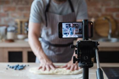 baker online courses. food preparing and culinary training class concept. smiling bearded chef kneading dough in the kitchen and shooting video of himself using mobile phone on a tripod. (CNW Group/Thinkific Labs Inc.)