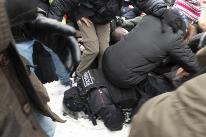 Demonstrators sit on a policeman lying in the snow during a protest against the jailing of opposition leader Alexei Navalny in Pushkin square in Moscow, Russia, Saturday, Jan. 23, 2021. Russian police arrested more than 3,400 people Saturday in nationwide protests demanding the release of opposition leader Alexei Navalny, the Kremlin's most prominent foe, according to a group that counts political detentions. In Moscow, an estimated 15,000 demonstrators gathered in and around Pushkin Square in the city center, where clashes with police broke out and demonstrators were roughly dragged off by helmeted riot officers to police buses and detention trucks. Some were beaten with batons. (AP Photo/Viktor Berezkin)