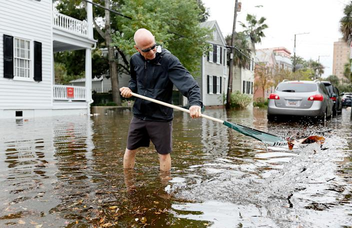 Rob Kramer removes debris from a drain as tidal flooding inundated many downtown streets in Charleston, S.C., on Oct. 27, 2015, in Charleston, S.C. Just weeks after historic rains drenched the state, more flooding along the South Carolina coast brought another round of astronomical high tides often called king tides.