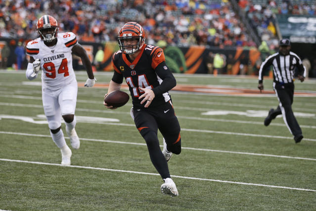 Cincinnati Bengals quarterback Andy Dalton (14) rushes for a 5-yard touchdown during the first half of an NFL football game against the Cleveland Browns, Sunday, Dec. 29, 2019, in Cincinnati. Browns defensive end Bryan Cox (94) watches. (AP Photo/Gary Landers)