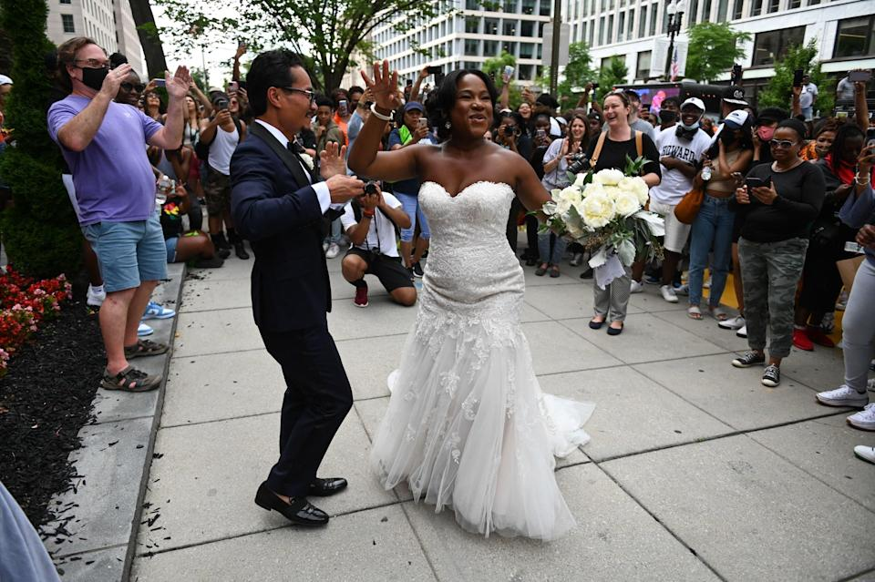 A bride and groom dance as they walk past people celebrating Juneteenth at the Black Lives Matter Plaza in Washington, DC.
