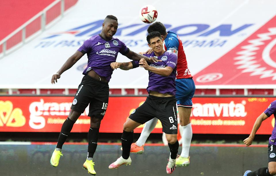 Jesus Molina (R) of Guadalajara jumps for a header with Jose Ortiz (L) and Roberto Meraz of Mazatlan during their pre-season Copa por Mexico football tournament match at the Akron stadium in Zapopan, Metropolitan Guadalajara, Jalisco State, Mexico, on July 11, 2020, amid the COVID-19 novel coronavirus pandemic. - The tournament is played without spectators as a preventive measure against the spread of COVID-19. (Photo by Ulises RUIZ / AFP) (Photo by ULISES RUIZ/AFP via Getty Images)