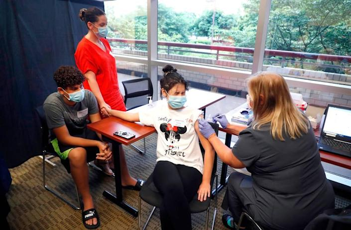 Ismelda Rosario holds her daughter's hand, Yismel Gonzalez, 12, as she get her COVID-19 vaccine from Pam Scott, RN, during the WakeMed Back-to-School Blitz vaccine clinic at the WakeMed Raleigh Campus in Raleigh, N.C., Sunday, August 1, 2021. Yismel's brother, Franklin Gonzalez, 13, left, watches.