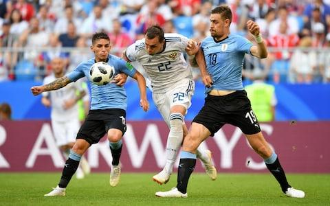 Artem Dzyuba of Russia challenge for the ball with Lucas Torreira and Sebastian Coates of Uruguay during the 2018 FIFA World Cup Russia group A match between Uruguay and Russia at Samara Arena on June 25, 2018 in Samara, Russia - Credit: Getty Images