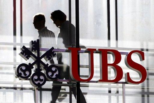 Employees walk past a logo of the Swiss banking giant UBS on October 30, 2012 in Zurich