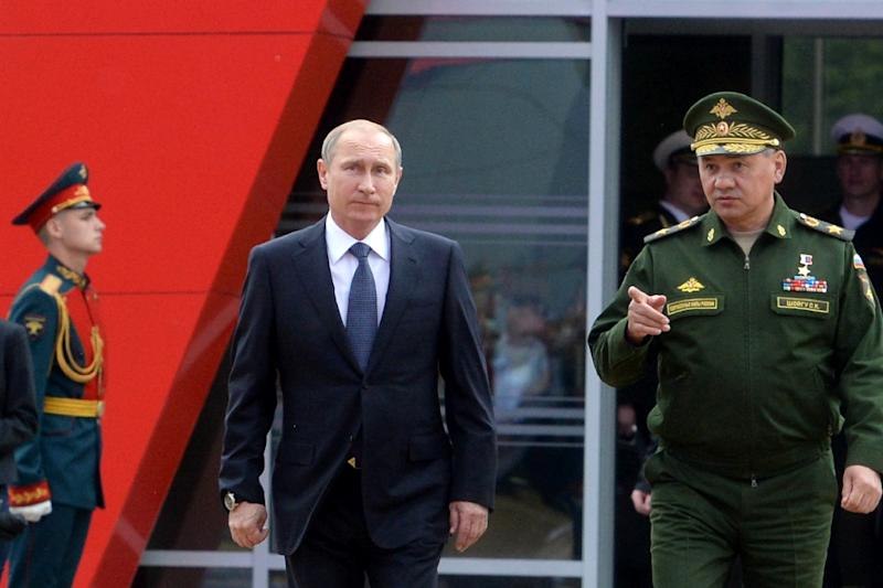 Russian President Vladimir Putin (C) and Defence Minister Sergei Shoigu arriving at an international military forum in Kubinka, outside Moscow, on June 16, 2015