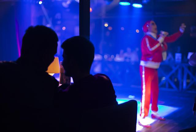 In this photo taken Saturday, Feb. 8, 2014, two men watch a performance at the Mayak cabaret, the most reputable gay club in Sochi, Russia, host to 2014 Winter Olympics. Russia adopted a law last year, prohibiting vaguely defined propaganda of non-traditional sexual relations and pedophilia. The legislation makes it illegal to disseminate information to children even if it merely shows that gay people are just like everybody else. At Mayak, packed on Saturday night, gay men and women steered away from discussing the law, preferring to enjoy life, closeted as it is. About a hundred people were chatting at the bar, sitting in armchairs or dancing. Couples were sharing kisses. Everyone was waiting for the club's specialty: a drag show. At 1.30 a.m. on Sunday, the music stopped and the show began. (AP Photo/David Goldman)
