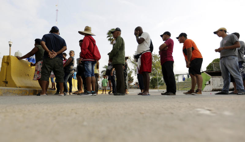 "FILE - In this April 30, 2019, file photo, migrants seeking asylum in the United States line up for a meal provided by volunteers near the international bridge in Matamoros, Mexico. The U.S. government will expand its policy requiring asylum seekers to wait outside the country in one of Mexico's most dangerous cities. According to officials for two congressional Democrats, the Department of Homeland Security says it will implement its ""Migrant Protection Protocols"" in Brownsville, Texas, across the border from Matamoros, Mexico. Matamoros is in Mexico's Tamaulipas state, which the U.S. government warns citizens not to visit due to violence and kidnappings. (AP Photo/Eric Gay, File)"