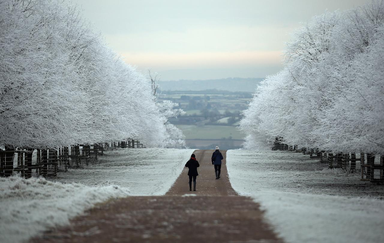BATH, UNITED KINGDOM - DECEMBER 12:  People are seen out for a walk as frost lingers on the trees at Dyrham Park on December 12, 2012 near Bath, England. Forecasters have warned that the UK could experience the coldest day of the year so far today, with temperatures dropping as low as -14C, bringing widespread ice, harsh frosts and freezing fog. Travel disruption is expected with warnings for heavy snow in some parts of the country.  (Photo by Matt Cardy/Getty Images)