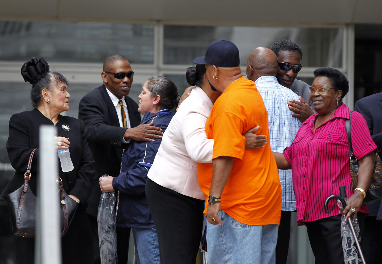 Family members and supporters of victims who were killed by New Orleans police hug each other outside Federal Court after sentences were handed out in the case Wednesday, April 4, 2012 in New Orleans. Five former New Orleans police officers were sentenced to prison terms ranging from six to 65 years for their roles in deadly shootings of unarmed residents in the chaotic days after Hurricane Katrina, with the judge lashing out at prosecutors for two hours on their handling of the case. (AP Photo/Gerald Herbert)