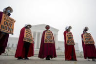 """Activists opposed to the confirmation of President Donald Trump's Supreme Court nominee, Judge Amy Coney Barrett, dressed as characters from """"The Handmaid's Tale,"""" protest at the Supreme Court on a foggy day, Thursday, Oct. 22, 2020 in Washington. (AP Photo/Jose Luis Magana)"""