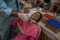A health worker takes a nasal swab sample of a passenger to test for COVID-19 at a bus terminal in New Delhi, India, Wednesday, March 24, 2021. (AP Photo/Altaf Qadri)