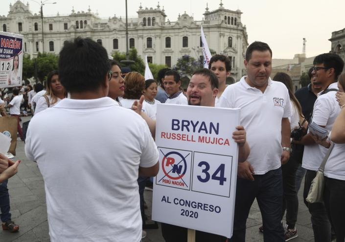 """In this Dec. 13, 2019 photo, congressional candidate Bryan Russell, who has Down syndrome, campaigns amid others from his party at San Martin Plaza in Lima, Peru. """"I want people with my condition to have a voice,"""" said Russell, who studied communications at the Peruvian San Ignacio de Loyola university and said his parents encouraged him to find his own way. (AP Photo/Martin Mejia)"""