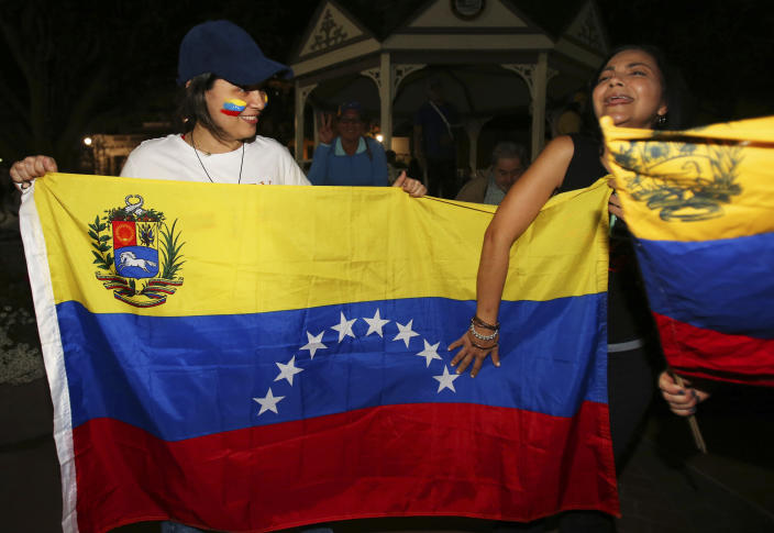 Katiry Ochoa, left, and Yalitza Lozano hold a flag from Venezuela, as they protest against Venezuelan President Nicolas Maduro with about 150 other people on the Ocala Downtown Square in Ocala, Fla., Wednesday, Jan. 23, 2019. The protestors in Ocala joined thousands of Venezuelans who took to the streets in Caracas, Venezuela, Wednesday, answering the opposition's call for a nationwide protest to rid Maduro from the office. (Bruce Ackerman/Star-Banner via AP)