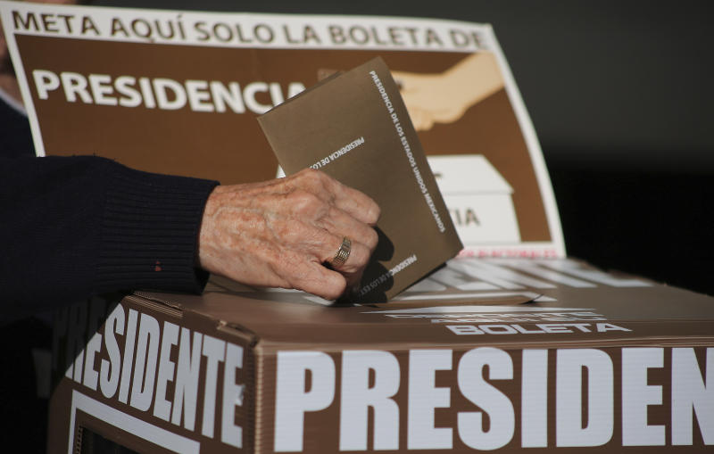 An elderly woman votes for president during general elections in Queretaro, Mexico, Sunday, July 1, 2018. Sunday's elections for posts at every level of government are Mexico's largest ever and have become a referendum on corruption, graft and other tricks used to divert taxpayer money to officials' pockets and empty those of the country's poor. (AP Photo/Christian Palma)
