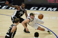 Los Angeles Clippers forward Kawhi Leonard (2) defends against Dallas Mavericks guard Luka Doncic (77) during the fourth quarter of Game 7 of an NBA basketball first-round playoff series Sunday, June 6, 2021, in Los Angeles, Calif. (AP Photo/Ashley Landis)