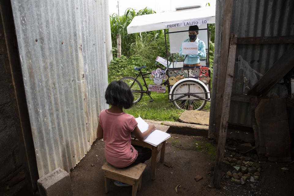 Gerardo Ixcoy teaches 12-year-old student Paola Ximena Conoz about fractions from his mobile classroom, parked just outside the door to her home in Santa Cruz del Quiche, Guatemala, Wednesday, July 15, 2020. Each day the 27-year-old sets out pedaling among the cornfields of Santa Cruz del Quiche to give individual instruction to his sixth-grade students. (AP Photo/Moises Castillo)