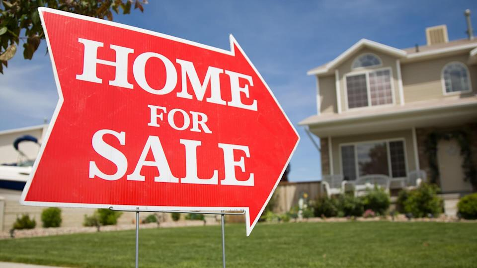 """An arrow shaped red """"Home For Sale"""" sign in front of a suburban 2-story home."""