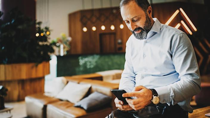 Mature businessman text messaging on mobile phone at office.