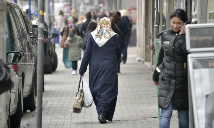 """In this picture taken March 7, 2013, Turkish immigrants walk the shopping streets in Dusiburg-Marxloh, western Germany.Germany's experience with """"guest workers"""" offers lessons for the United States as it debates immigration reform, including whether to provide a path to citizenship for unskilled foreign laborers. (AP Photo/Martin Meissner)"""