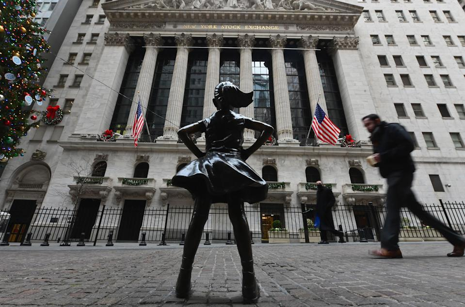 People walk past the New York Stock Exchange (NYSE) and 'Fearless Girl' statue at Wall Street on December 9, 2020 in New York City. (Photo by Angela Weiss / AFP) (Photo by ANGELA WEISS/AFP via Getty Images)