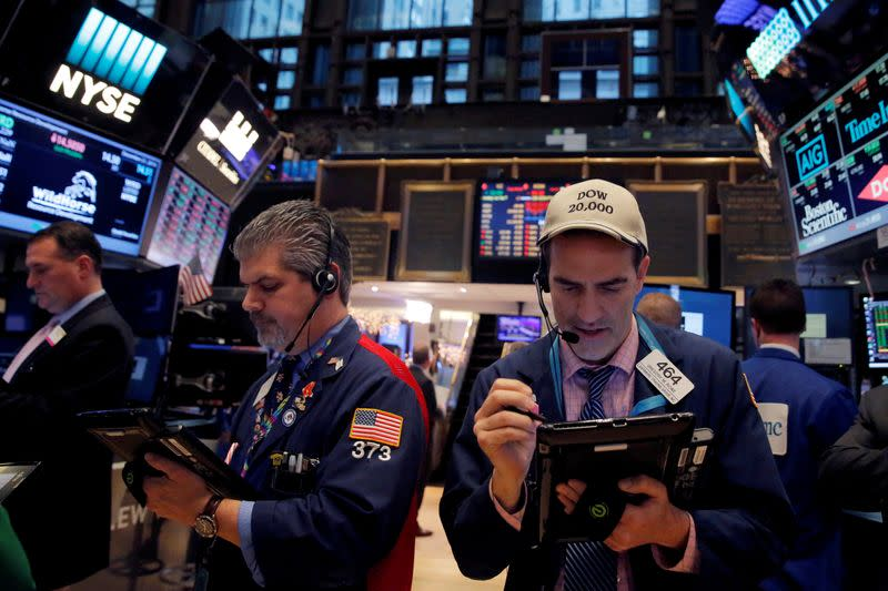 FILE PHOTO: Traders work on the floor at the New York Stock Exchange (NYSE) in Manhattan, New York City, U.S.