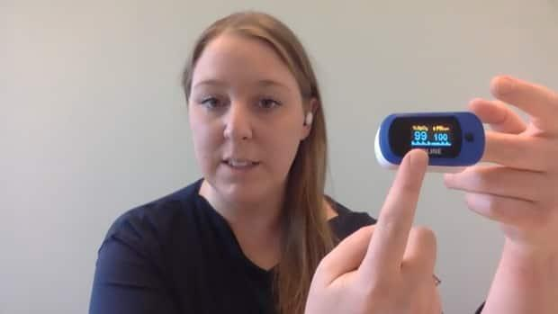 Dr. Ashley Miller, the chief medical information officer for Nova Scotia, demonstrates how to use a pulse oximeter. This simple device shows her oxygen level is at 99 per cent. It's how the province is monitoring COVID-19 patients who are at home.  (Carolyn Ray/CBC - image credit)