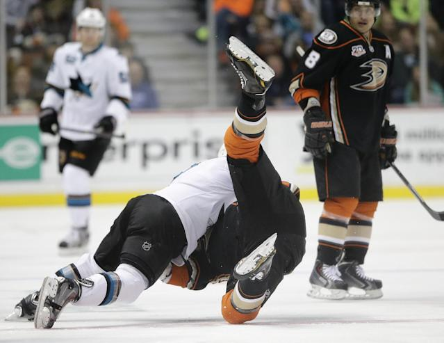San Jose Sharks' Mike Brown, left, takes down Anaheim Ducks' Patrick Maroon during the first period of an NHL hockey game on Tuesday, Dec. 31, 2013, in Anaheim, Calif. (AP Photo/Jae C. Hong)