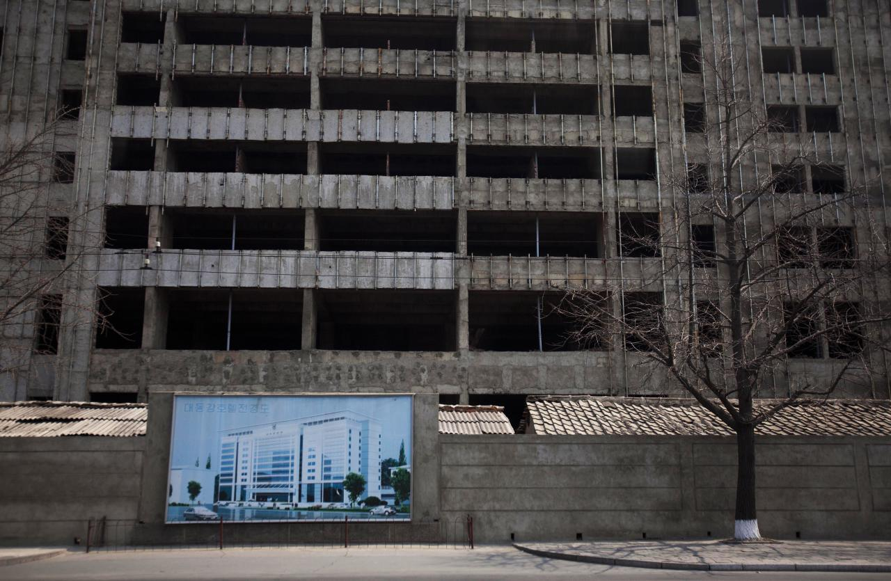 In this April 13, 2011 photo, an illustration of a building project hangs in front of the construction project in progress in Pyongyang, North Korea. (AP Photo/David Guttenfelder)