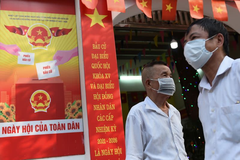 FILE PHOTO: People stand around a place that will be a polling station for the upcoming elections in Hanoi