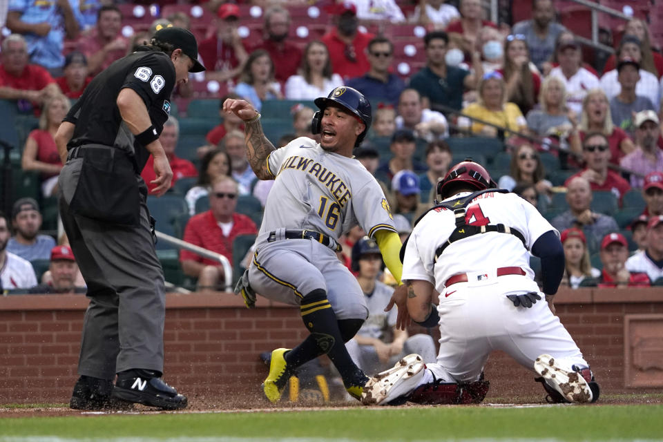 Milwaukee Brewers' Kolten Wong (16) is tagged out at home by St. Louis Cardinals catcher Yadier Molina as home plate umpire Chris Guccione (68) watches the play during the first inning of a baseball game Tuesday, Aug. 17, 2021, in St. Louis. (AP Photo/Jeff Roberson)