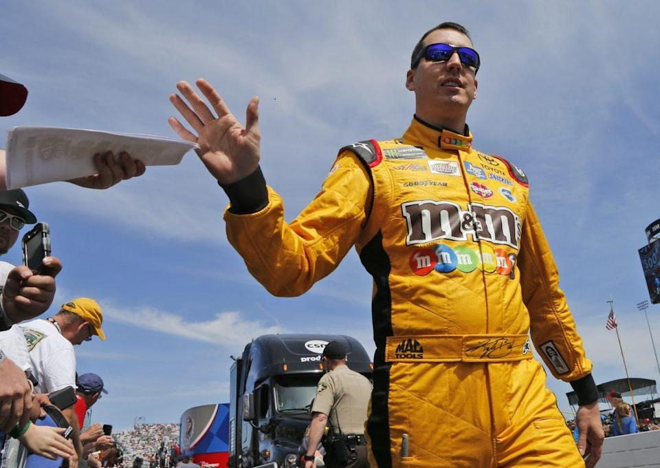 Kyle Busch greets fans during driver introductions prior to the start of the NASCAR Cup Series auto race at Martinsville Speedway in Martinsville, Va., Sunday, April 2, 2017. (AP Photo/Steve Helber)