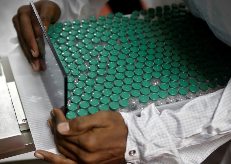 FILE PHOTO: An employee in personal protective equipment (PPE) removes vials of AstraZeneca's COVISHIELD, coronavirus disease (COVID-19) vaccine from a visual inspection machine inside a lab at Serum Institute of India, in Pune
