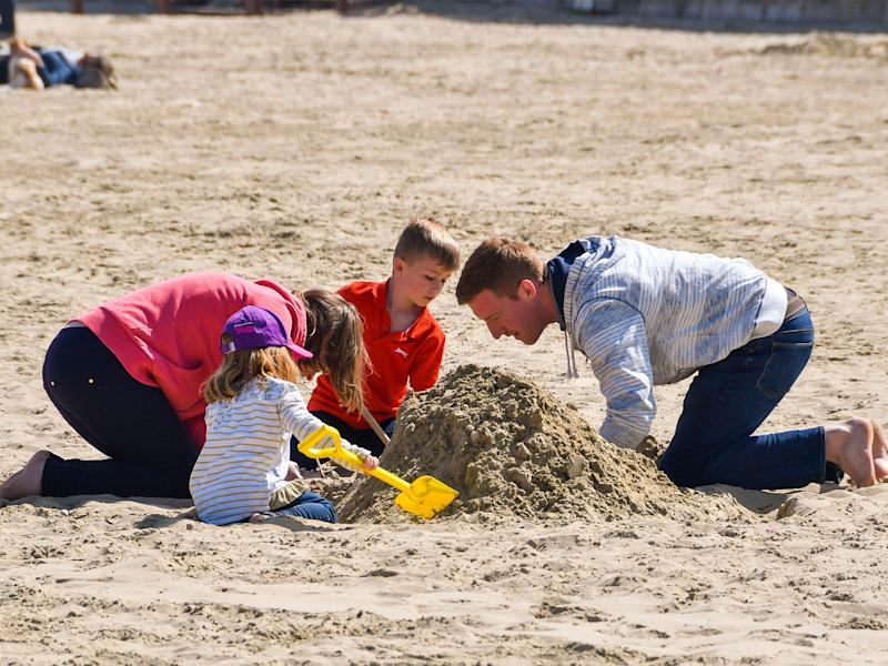 Balmy Britain: beachgoers in Weymouth, Dorset build a sandlecastle on Friday, as the weather warms: Alamy