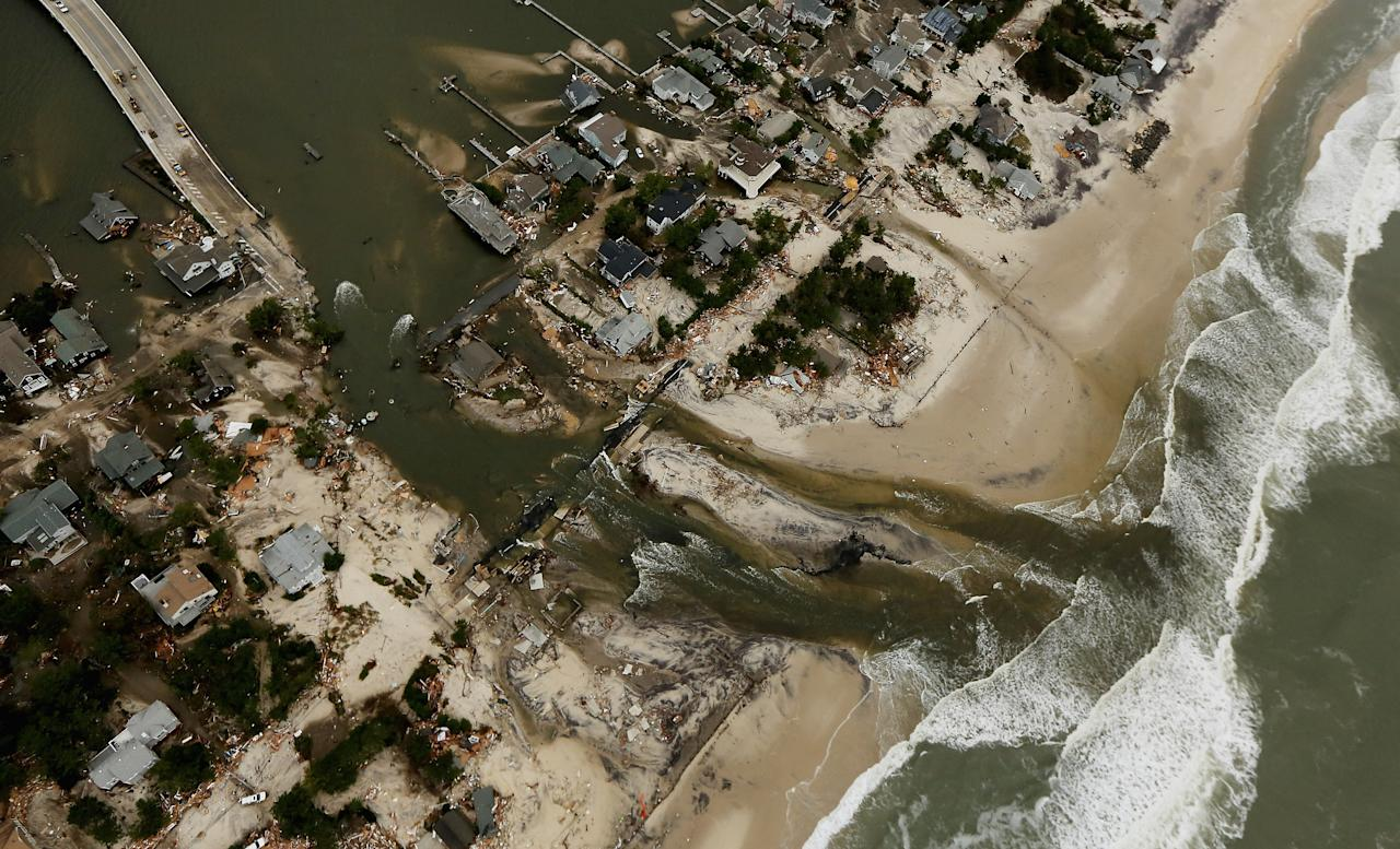 Homes sit in ruin at the end of a bridge (L) wrecked by flooding from Superstorm Sandy on October 31, 2012 in Mantoloking, New Jersey.  At least 50 people were reportedly killed in the U.S. by Sandy with New Jersey suffering massive damage and power outages.  (Photo by Mario Tama/Getty Images)