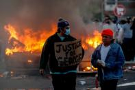 FILE PHOTO: A man wearing a face mask holds a sign near a burning vehicle at the parking lot of a Target store during protests in Minneapolis