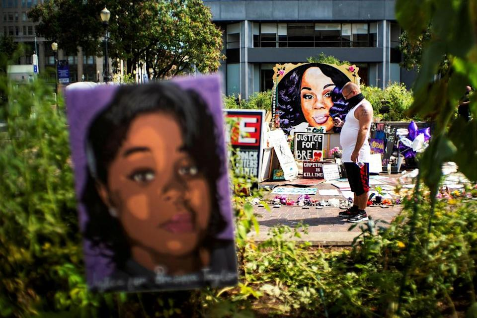 A man pauses at the memorial of Breonna Taylor before a march, after a grand jury decided not to bring homicide charges against police officers involved in the fatal shooting.
