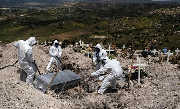 Workers wearing protective gear bury an unclaimed COVID-19 victim, at a municipal cemetery in Tijuana, Mexico (AFP Photo/Guillermo Arias)