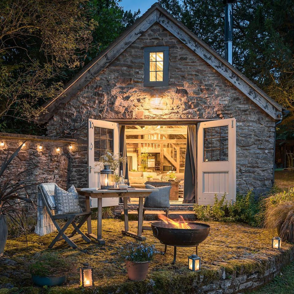 "<p>We are at Wishbone Cottage in the Malvern Hills. With stunning views, this home is quite the Tardis. The alfresco lighting, fire pit and seating area make the outdoor space just as cosy as the plush inside. The soft textures perfectly juxtapose the exposed beams and stone walls. This is a dream bolthole, surely? Wishbone Cottage is available through Unique Homestays. </p><p><a class=""link rapid-noclick-resp"" href=""https://www.uniquehomestays.com/self-catering/uk/worcestershire/malvern-hills/wishbone/"" rel=""nofollow noopener"" target=""_blank"" data-ylk=""slk:BOOK NOW"">BOOK NOW</a></p>"