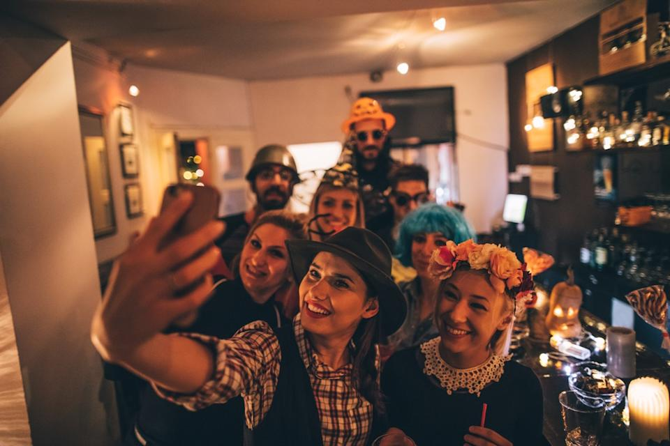 Group of costumed people having fun and making selfies on Halloween party