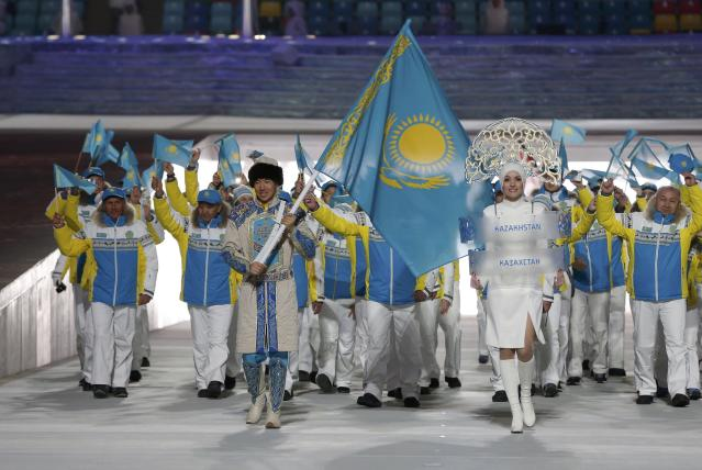 Kazakhstan's flag-bearer Yerdos Akhmadiyev leads his country's contingent during the opening ceremony of the 2014 Sochi Winter Olympics, February 7, 2014. REUTERS/Phil Noble (RUSSIA - Tags: OLYMPICS SPORT)