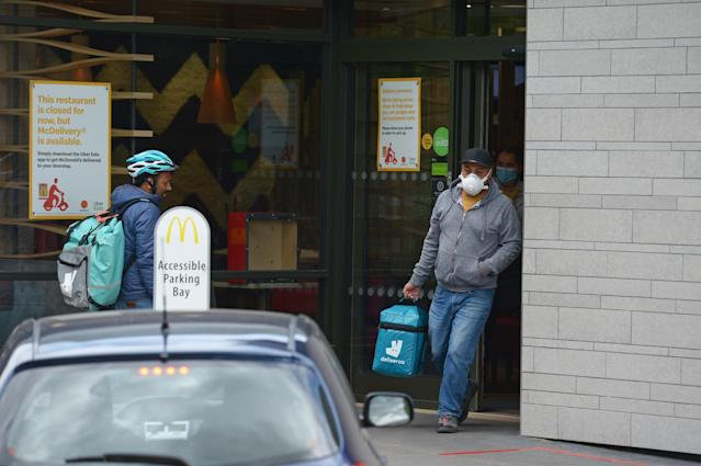 Deliveroo workers at a branch of McDonald's in Boreham, Chelmsford, Essex, one of 15 of the restaurant chain locations to have reopened for takeaway. (PA)