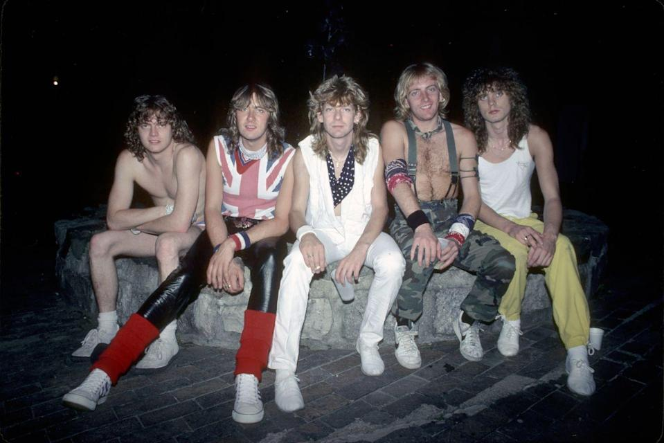 """<p>Formed in the late 70s in the UK, the band hit it big stateside with their hit song """"Bringin' On the Heartbreak,"""" and then followed that up with the album """"Pyromania."""" But it was their third album """"Hysteria"""" that was jam-packed with hits like """"Pour Some Sugar On Me"""" and """"Love Bites."""" Original band members were Pete Willis, Rick Savage, Joe Elliot and Tony Kenning. Though Kenning left before the band hit it big, and was replaced by young drummer Rick Allen, who lost one arm in a car accident in 1984 but quickly found a way to still rock with a custom drum kit and playing more with his feet. Also fairly early on Willis was replaced by Phil Collen and in 1991, guitarist Clark died of a drug overdose, and was replaced by Vivian Campbell. </p>"""