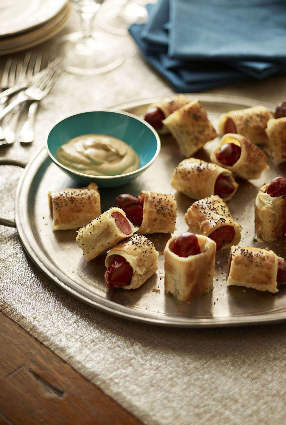 """<p>Some classics never fail to score with the party crowd. And they're so simple to make that it's a win-win. </p><p><strong><a href=""""https://www.countryliving.com/food-drinks/recipes/a3263/pigs-in-blanket-recipe/"""" rel=""""nofollow noopener"""" target=""""_blank"""" data-ylk=""""slk:Get the recipe"""" class=""""link rapid-noclick-resp"""">Get the recipe</a>.</strong></p>"""