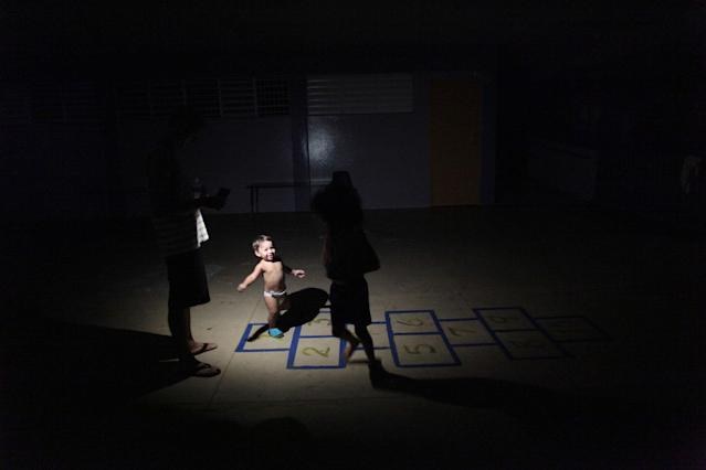 <p>Children play in the light of a flashlight at a school turned shelter, after their home was destroyed when Hurricane Maria hit the island in September, in Toa Baja, Puerto Rico, Oct.18, 2017. (Photo: Alvin Baez/Reuters) </p>