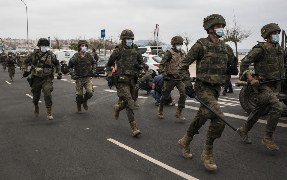 Spanish Army soldiers run as they take positions at the border of Morocco and Spain, at the Spanish enclave of Ceuta, on Tuesday, May 18, 2021. (AP Photo/Javier Fergo)