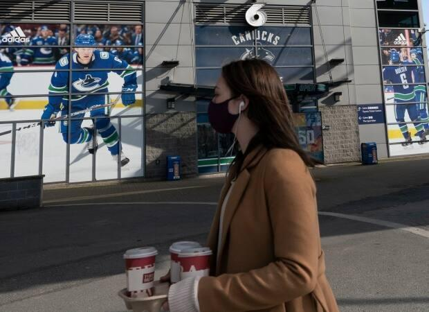 A woman wearing a protective face covering walks past Rogers Arena in downtown Vancouver. A total of 26 Canucks players and coaches tested positive during the COVID-19 outbreak that involved a variant of the virus.